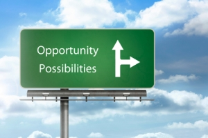 Opportunity and possibilities written over a signpost with blue sky in the background
